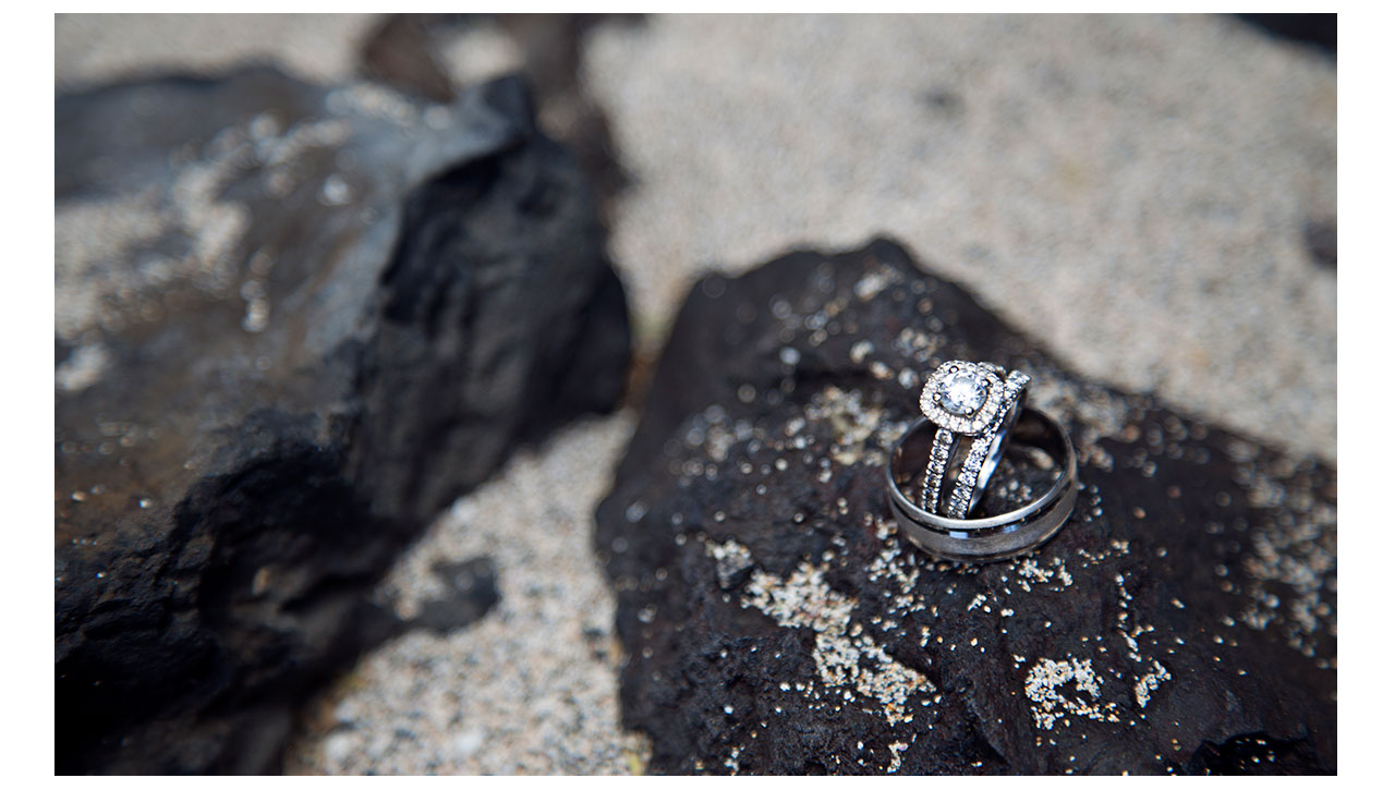 Rings on heart shaped rock in sand