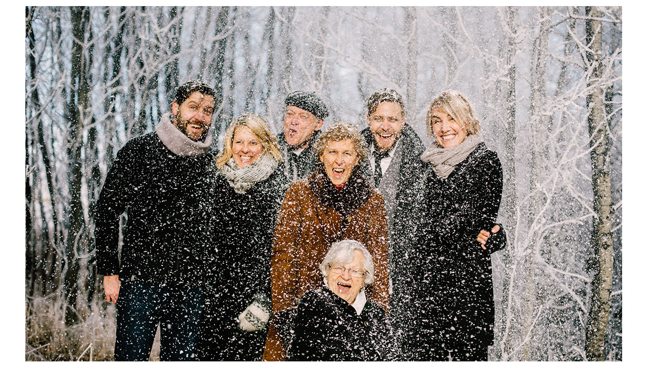Family posing while snowing