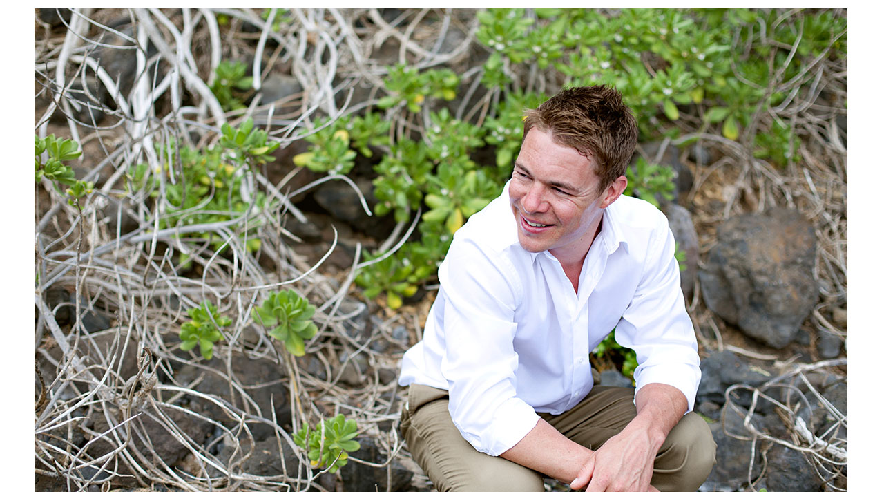 Groom sitting in lush green plants in Maui