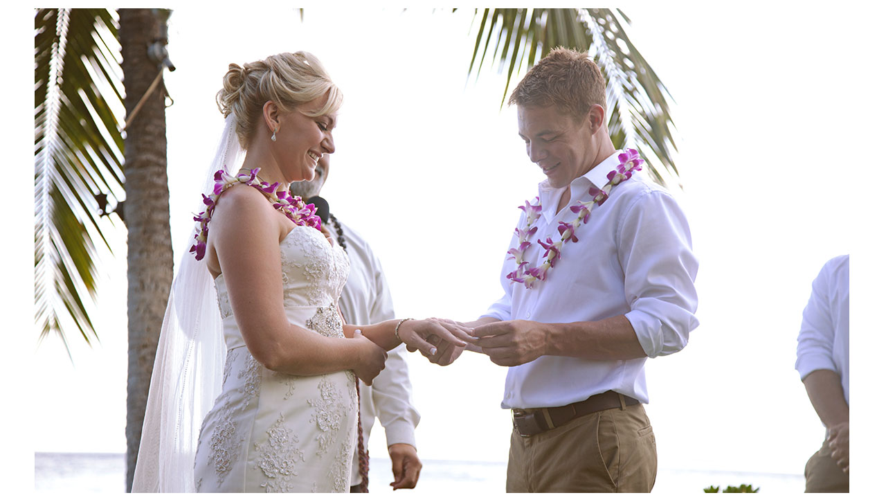 Husband putting ring on wife in Maui
