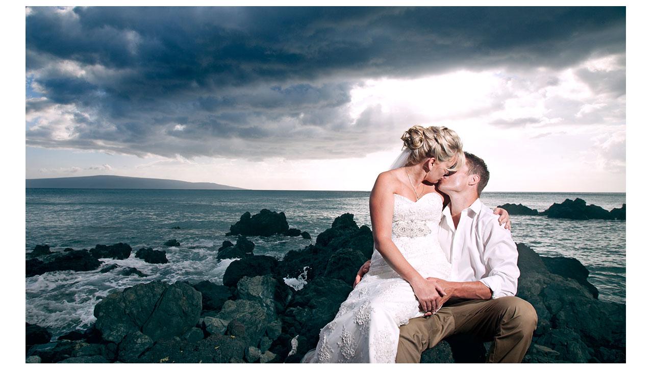 Couple kissing on lava rock Maui